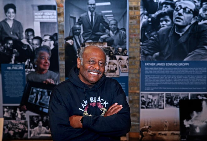 Clayborn Benson, the founder of the Wisconsin Black Historical Society and Museum, is helping to preserve critical history about African Americans. He is photographed against a backdrop of historical images documenting the civil rights movement in Milwaukee and around the state.