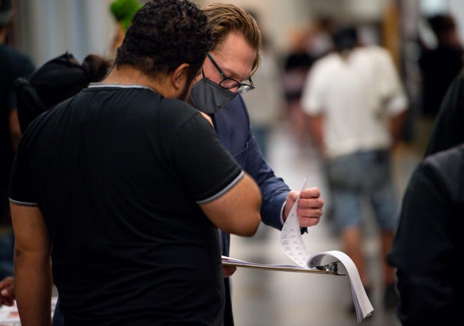 The General Sessions Music City Community Court Resource Services Coordinator Craig Holcomb looks over a clipboard of information as he assists someone in the hallway outside the courtrooms where eviction proceedings are happening in the Justice A. A. Birch Building in Nashville, Tenn., on Tuesday, Aug. 3, 2021.