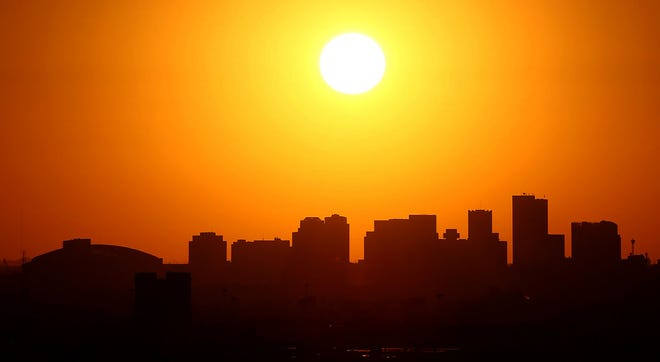 The sun passes behind downtown Phoenix in 2019.