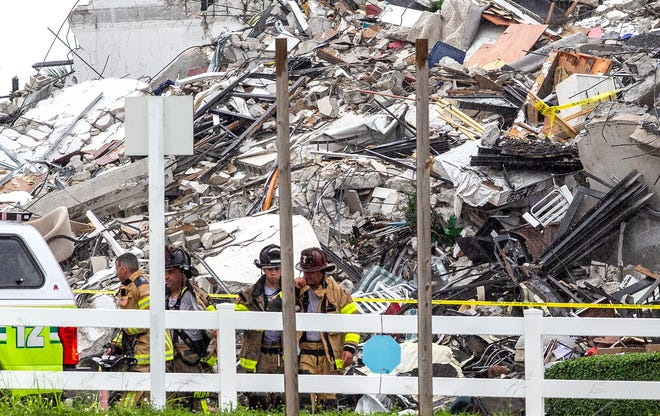 Miami-Dade County Fire Rescue firefighters are seen by piles of rubble of the Champlain Towers South Condo in Surfside, Florida. The building collapsed on June 24, 2021. (Pedro Portal/Miami Herald/TNS)