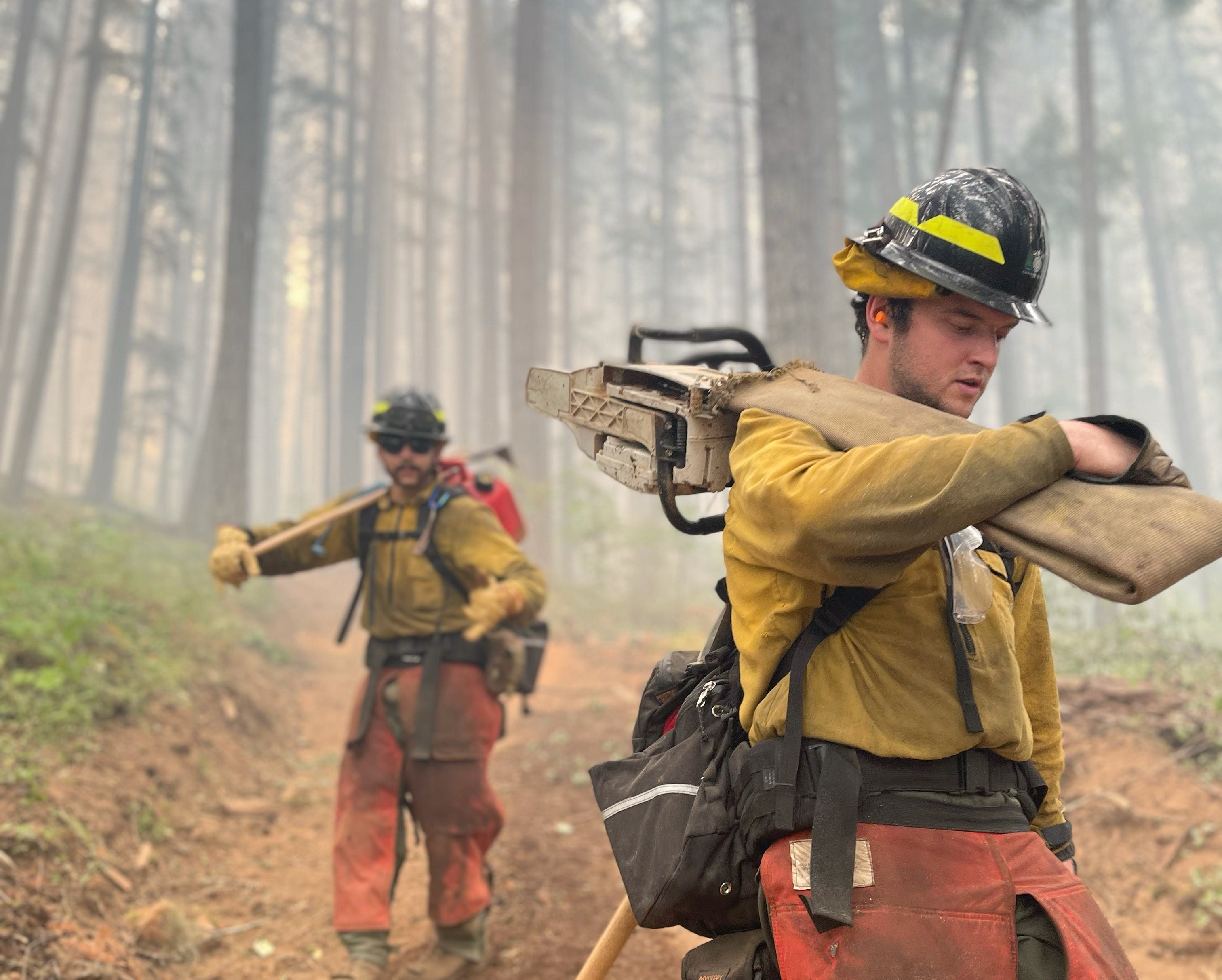 Members of a new hand crew from Clackamas County, Ore., hike down into a drainage with equipment to build a fire line on the Jack Fire in Southern Oregon this year