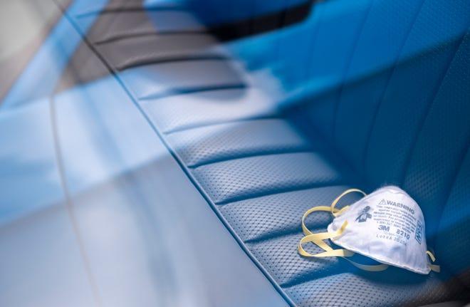 Una mascarilla N95 sobre el asiento de pasajeros de un Mercedes-Benz antiguo estacionado dentro del Club Pasadera Golf & Country en Monterey, California, el jueves 5 de agosto de 2021.