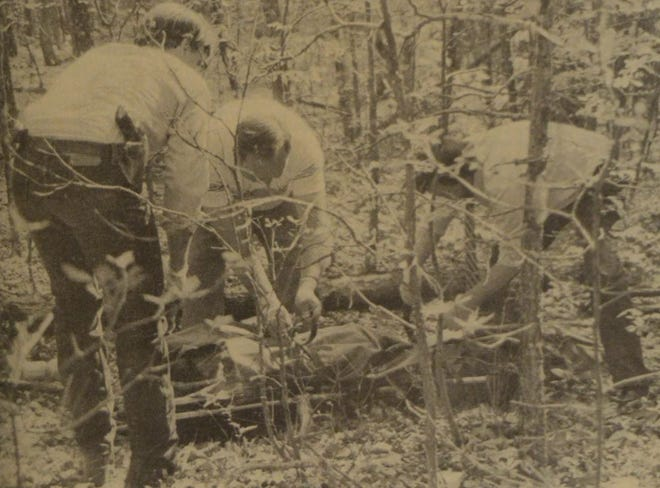The body of an unidentified murder victim (later determined to be Ronnie Johnson) is strapped to a gurney by (left to right) Douglas County Sheriff Roldan Turner, Bill Wisner of Klinkingbeards Funeral Home in Ava, and Quill Publisher Frank L. Martin III.