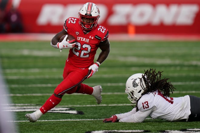FILE - In this Dec. 19, 2020, file photo, Utah running back Ty Jordan (22) runs for a score as he eludes a tackle by Washington State linebacker Jahad Woods (13) during the second half of an NCAA college football game in Salt Lake City. This was supposed to be Jordan's time. Instead, Utah approaches a new football season facing the unexpected and unwanted challenge of replacing Jordan in the backfield. Jordan died at 19 after an accidental shooting on Dec. 26.  (AP Photo/Rick Bowmer, File)