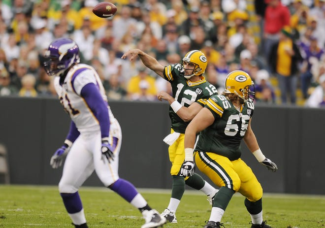 Green Bay Packers quarterback Aaron Rodgers throws behind the block of Mark Tauscher against the Minnesota Vikings at Lambeau Field on Sept. 8, 2008.