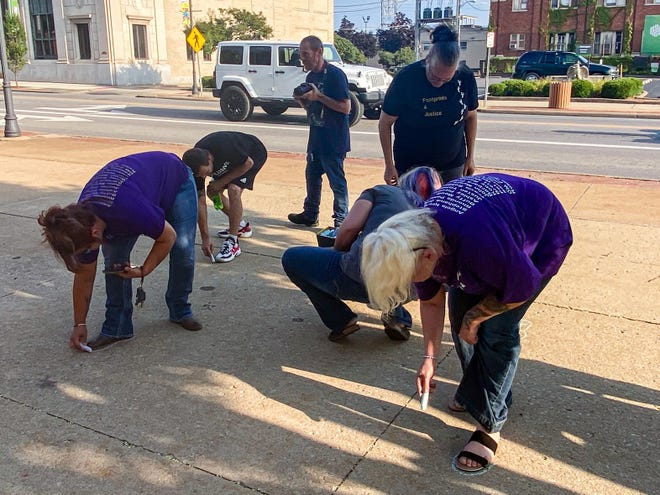 Members of Golden Hearts trace their footprints in honor of the missing and murders persons for whom they are seeking justice.