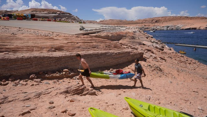 Visitors carry a kayak up a newly exposed cliff face beneath the closed Antelope Point launch ramp on Lake Powell on July 31, 2021, near Page, Arizona.