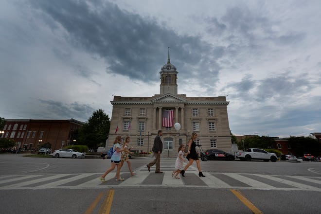 Pedestrians walk in front of the Maury County Courthouse during a First Fridays event in downtown Columbia, Tenn., on Friday, Aug., 8, 2021.