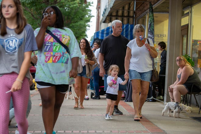 Penny Butler and her graddaughter Cate Bryan, 2, walk along West 7th Street with Mark Lewis during a First Fridays event in Columbia, Tenn, on Friday, Aug. 8, 2021.