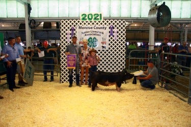 Joseph Johnson, owner of Dynamic Transportation in Monroe, holds a banner with his mother, Barb Johnson, after buying the grand champion 4-H hog for $17 a pound at the Monroe County Fair Friday night. Standing next to Barb is Ashton Albring of Monroe, who raised the pig.