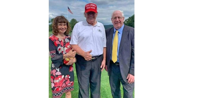 Former President Donald Trump is flanked by Massachusetts Republican Party Chairman Jim Lyons, right, and his wife, Bernadette,  in New York on Thursday, Aug. 5, 2021.
