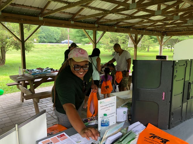 Xzy-Nayé Campbell, a Delaware River Fellow working at the Pocono Environmental Education Center this summer, fills a bag with informational items about PEEC on Saturday, Aug. 7, 2021.