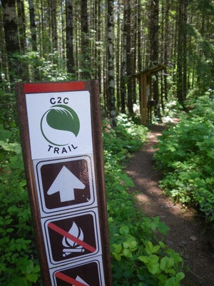 A Corvallis-to-the-Sea Trail signpost and trailhead kiosk.