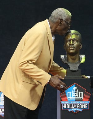 Class of 2020 member Harold Carmichael kisses his bust during the Pro Football Hall of Fame Enshrinement at Tom Benson Hall of Fame Stadium, Aug. 7, 2021, in Canton. (Charles LeClaire-USA TODAY Sports)