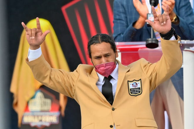 Troy Polamalu, a member of the Pro Football Hall of Fame Class of 2020, gestures after receiving his gold jacket during the enshrinement at the Pro Football Hall of Fame, Saturday, Aug. 7, 2021, in Canton, Ohio. (AP Photo/David Richard)