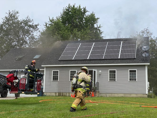 Firefighters prepare to raise the tower truck as smoke pours from the roof of a home at 1114 Gilbertville Road on Saturday in New Braintree.