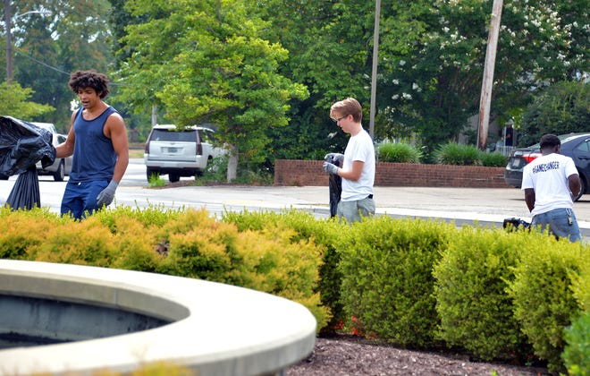 Trevor Willard, left, Brett Guessford and Malik Phillips pick up litter in front of Hagerstown City Park on Saturday morning as part of a citywide initiative inviting residents to help clean up trash on the streets.