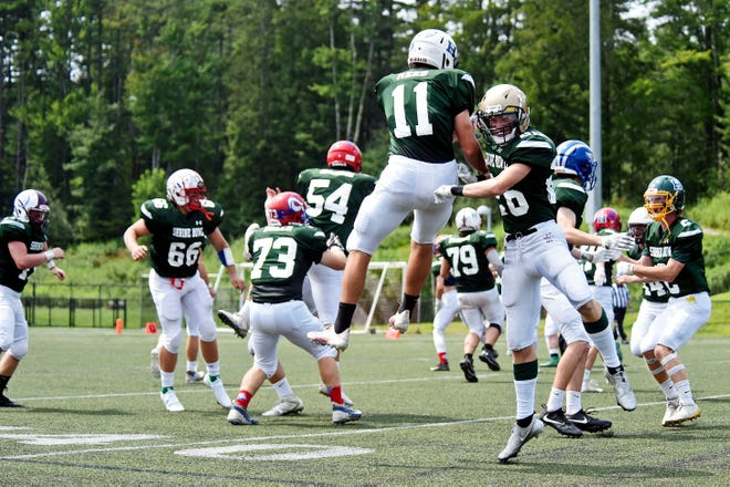 Vermont's Owen Abrahamsen, right, Evan Reed (11) and the Vermont defense celebrate a fourth-down stop during the 68th annual Shrine Maple Sugar Bowl at Castleton University's Dave Wolk Stadium on Saturday. New Hampshire won 21-0.