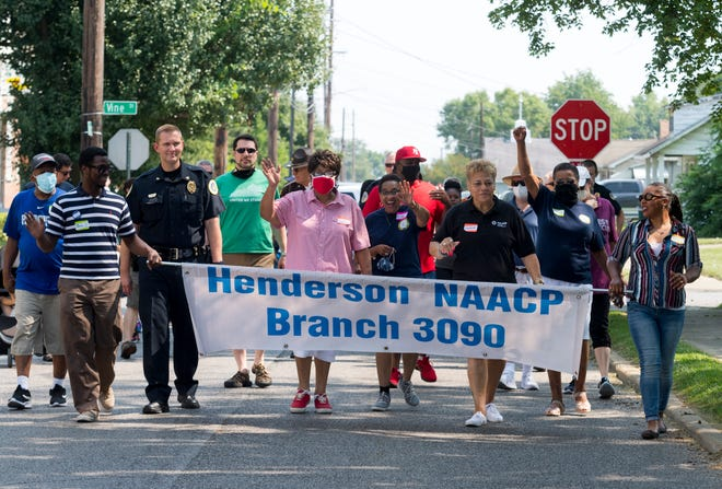 People head down South Alvasia Street during the Walking Toward Unity event hosted by the Henderson chapter of the NAACP in Henderson, Ky., Saturday morning, Aug. 7, 2021.