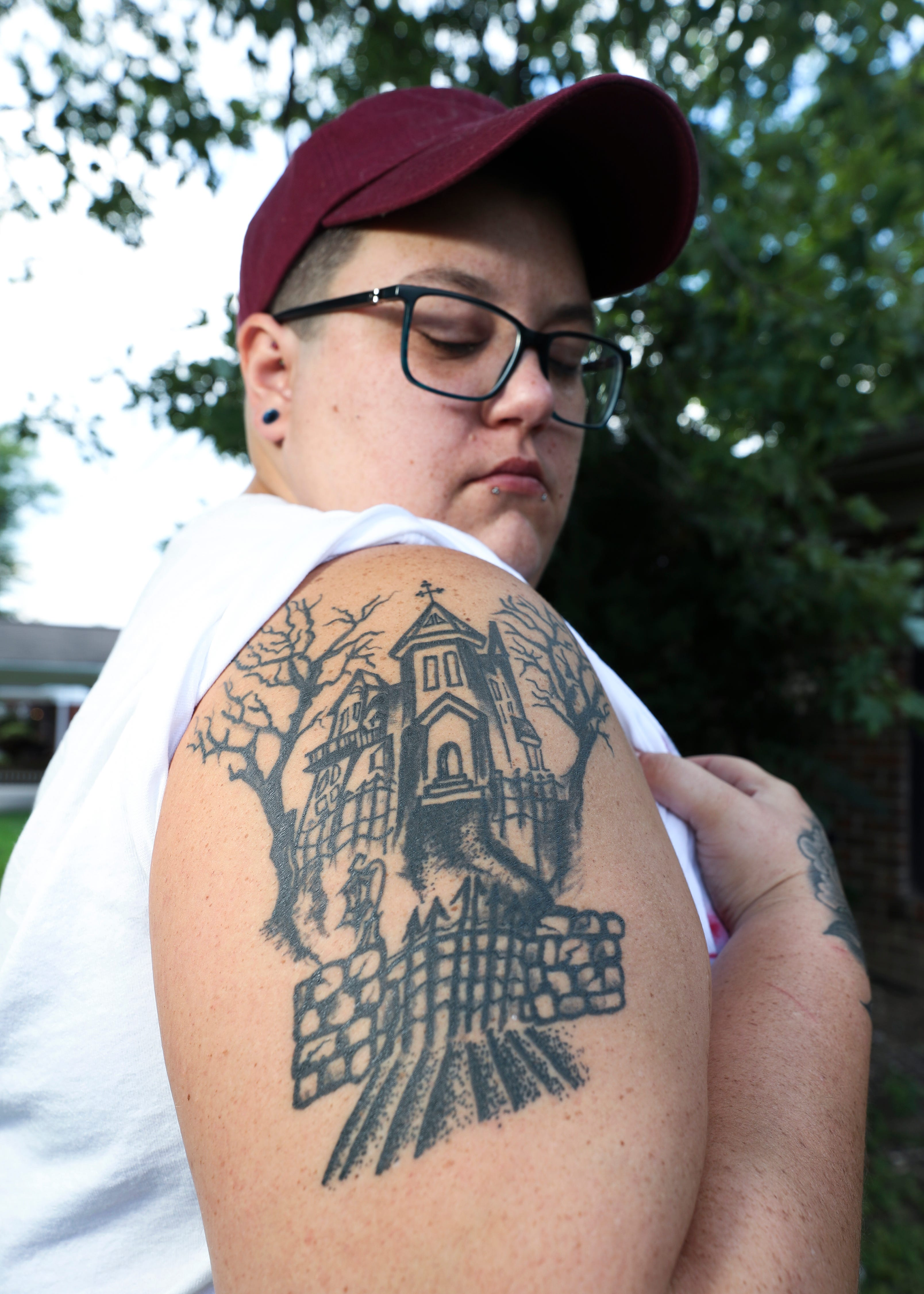 Lacy Hatfield wears a tattoo of a haunted house on her arm in honor of her 14-year-old nephew, Darrin Thiele III, at her home in Louisville, Ky. on Aug. 3, 2021.  They enjoyed celebrating Halloween together.  Darrin was shot dead in the St. Dennis neighborhood in April.  She helped raise him and thought of him as a son.