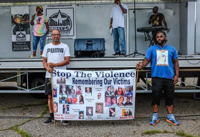 Marchers gather in a parking lot to hear speakers discuss gun violence in Lansing Saturday, August 7, 2021.