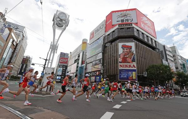 Runners move past the Susukino district while competing in the men's marathon final during the Tokyo 2020 Olympic Games in Sapporo on August 8, 2021.