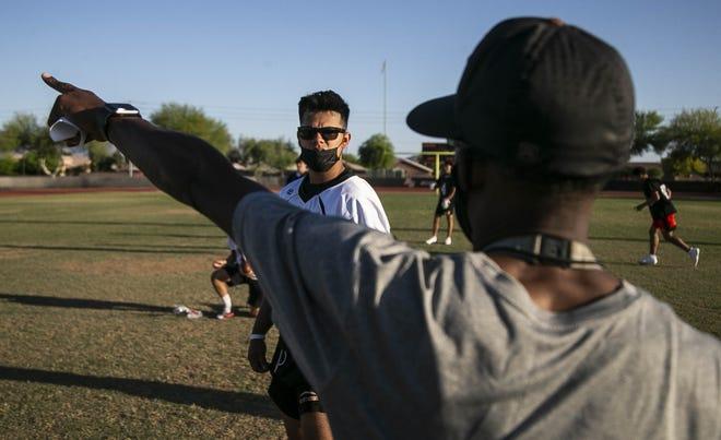 A player receives instructions during Desert Edge High School football spring drills.