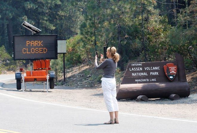 """Pam Wyss of Portland, Oregon, stops at the north entrance of Lassen National National Park off Highway 44 on Friday, Aug. 6, 2021, to take a picture of the closed sign for her cousin, who recently visited the park. """"I wanted to let her know the park was closed,"""" said Wyss, who was visiting in the area."""