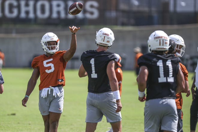 Texas running back Bijan Robinson throws the ball to quarterback Hudson Card (1) during practice on Saturday, Aug. 7, 2021, in Austin, Texas.