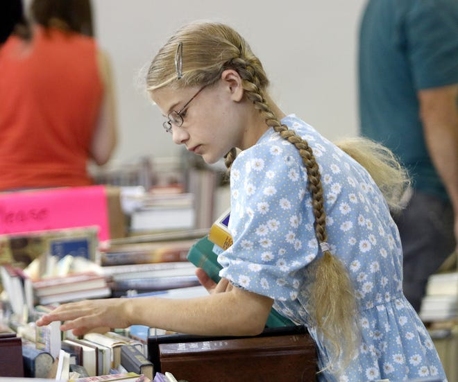 Lilly Vanpelt of Pennsylvania, who is visiting family in Alliance, looks through stacks of used books inside the gym of Alliance Neighborhood Center on Saturday, Aug. 7, 2021, during the first hours of the 2021 Greater Alliance Carnation Festival Friends of Rodman Library Used Book Sale.