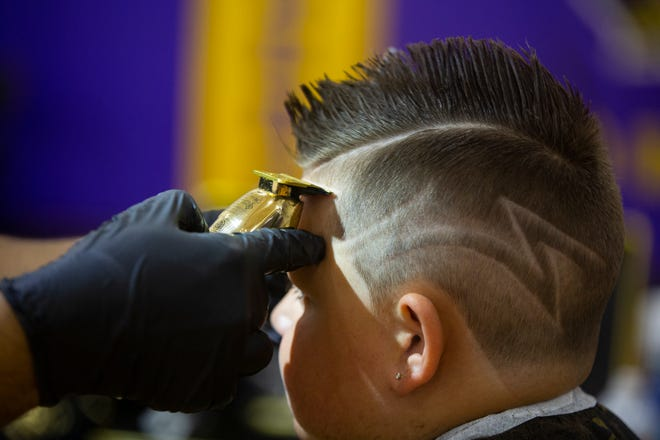 Reynoldsburg barber Danny Eustaquio cuts Rion Marioth, 5, hair during the Cops and Barbers event at the Reynoldsburg High School Sunday. Rion was so excited by the new do that he gave Eustaquio a big hug after showing it off to his family members.