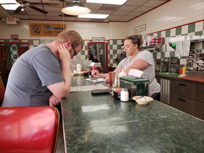 Waitress Brooke Towles takes a customer's order Aug. 7, 2021, at Wynn's Diner.