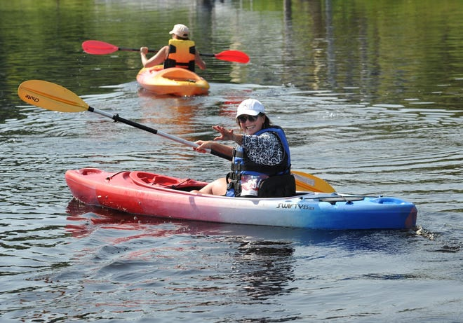Mary Anne McDonough of Norwell waves to onlookers as she heads to the starting line of The Great River Race in Norwell, Saturday, Aug. 7, 2021.