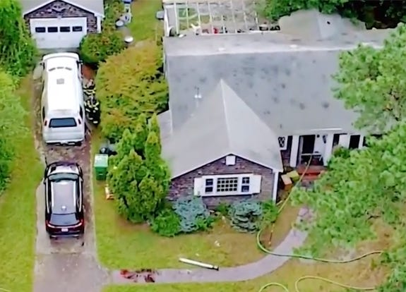 Firefighters on Cape Cod investigate a fatal fire Sunday at a house in Barnstable. A woman and a pet dog died. (WCVB)