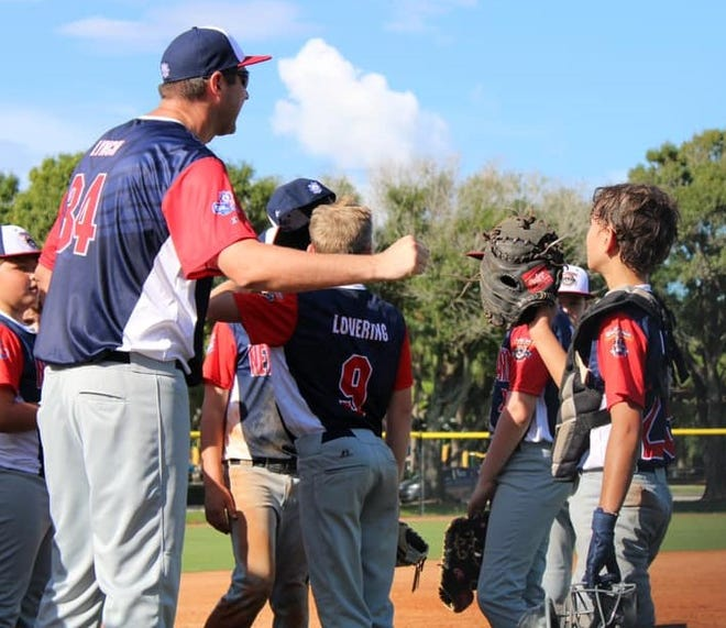 Dover head coach Mike Lynch talks to his team between innings during Sunday's game against South Lexington, Kentucky in the Cal Ripken 10-year-old World Series in Palm Beach Gardens, Florida. Dover lost 5-1 and will play Jacksonville, Florida on Monday.
