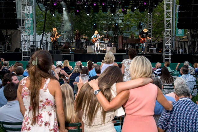 Fans embrace while Sheryl Crow performs during the Motor City Car Crawl Charity Gala at Campus Martius Park in Detroit.