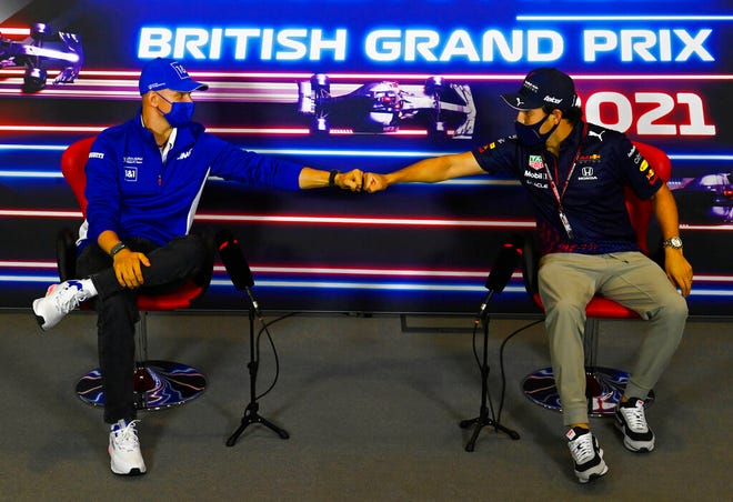 FILE - In this July 15, 2021 file photo, Haas driver Mick Schumacher of Germany, left, and Red Bull driver Sergio Perez of Mexico greet each other with a fist bump as they attend a media conference at the Silverstone circuit, Silverstone, England. As workers return to the office, friends reunite and more church services shift from Zoom to in person, this exact question is befuddling growing numbers of people: to shake or not to shake. (Mark Sutton, Pool Photo via AP, File)