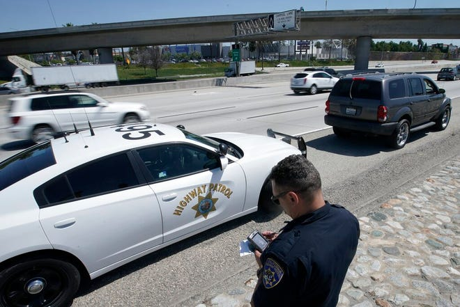 FILE - In this April 23, 2021 file photo, California Highway Patrol officer Troy Christensen runs a driver's license after stopping a motorist along Interstate 5 who was suspected of speeding in Anaheim, Calif. The number of highway deaths in 2020 was the greatest in more than a decade even though cars and trucks drove fewer miles during the pandemic, and motorists are continuing to speed, tailgate and zigzag through traffic. (AP Photo/Chris Carlson)