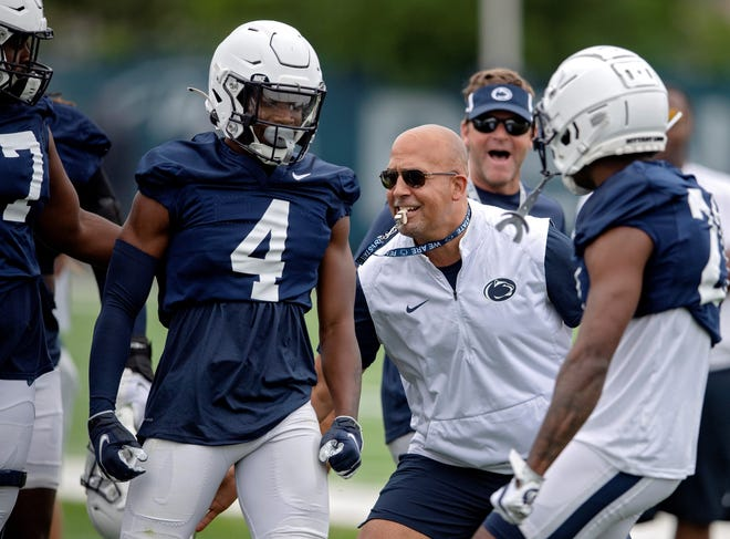 Penn State football coach James Franklin, second from front right, congratulates freshman cornerback Kalen King (4) after winning a 1-on-1 against a wide receiver during an NCAA college football practice Saturday, Aug. 7, 2021, in State College, Pa. (Abby Drey/Centre Daily Times via AP)