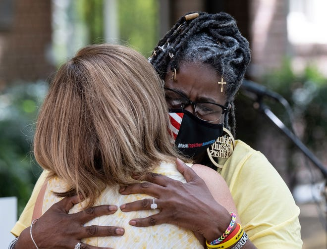 Marjorie Roberts, right, hugs Tanya Washington after speaking about how COVID affected her during a gathering at St. Luke's Episcopal Church in Atlanta on Saturday, Aug. 7, 2021, as part of National COVID Awareness Day.