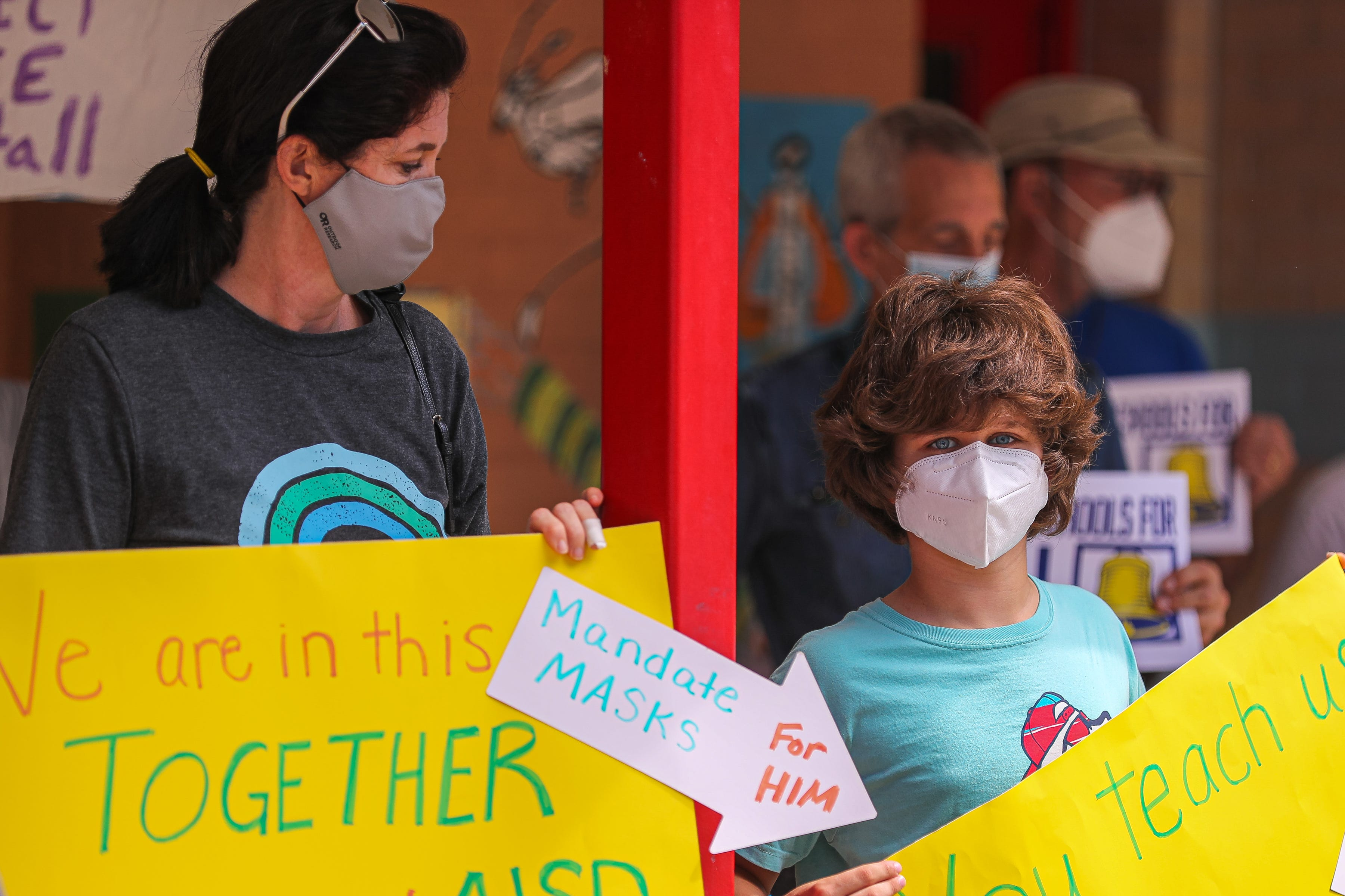 Milana Noueilaty stands with her son, Kaden, holding signs in support of mask mandates. Parents, teachers and medical experts held a press conference at Travis Heights Elementary on Aug. 9, 2021 to demand Austin Independent School District implement a mask mandate ahead of the 2021-2022 school year.
