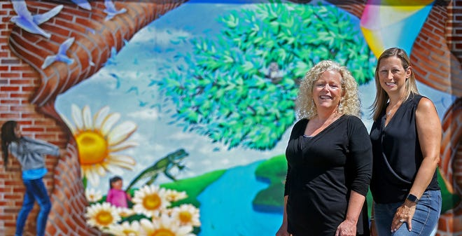 Adriana Caso, director of Door #2 Art Studio, left, and First & Main Marketing Director Debra Sherman pose for a photo in front of the mural that was installed in downtown Hudson. The mural was a collaboration between Door #2 Art Studio and First & Main.