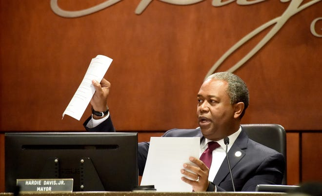 Augusta Mayor Hardie Davis holds up papers related to a parking meter proposal at a 2019 meeting.