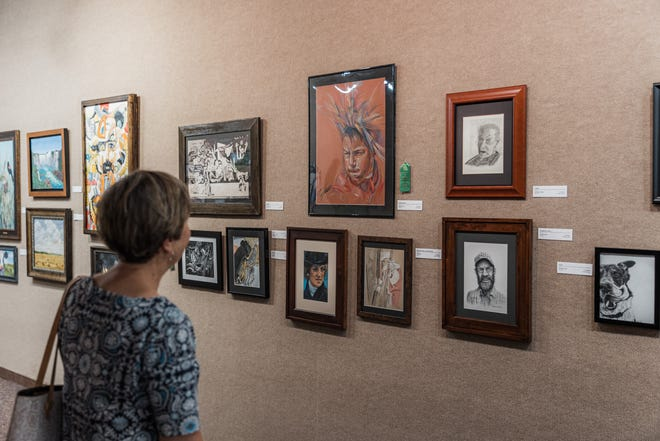 Creations from local artists catch the eye of Beth Fredrick in the Lyon Gallery at Bartlesville Community Center on Monday. The Bartlesville Art Association 2021 annual Art Show & Sale will conclude on Aug. 27, and admission to the gallery is free.