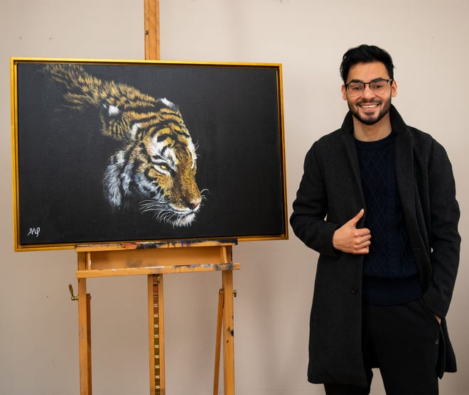 Hassan Qureshi with a painting now on display at 3060 Gallery