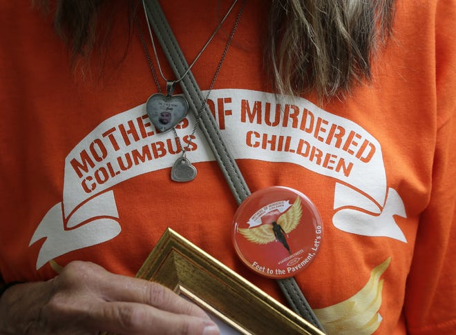 Brenda Johnson, 56, of the west side, holds a frame photograph of her son James Johnson III who was murdered in 2017, during a rally and march held by Mothers of Murdered Columbus Children at Columbus City Hall on Sunday, August 1, 2021.
