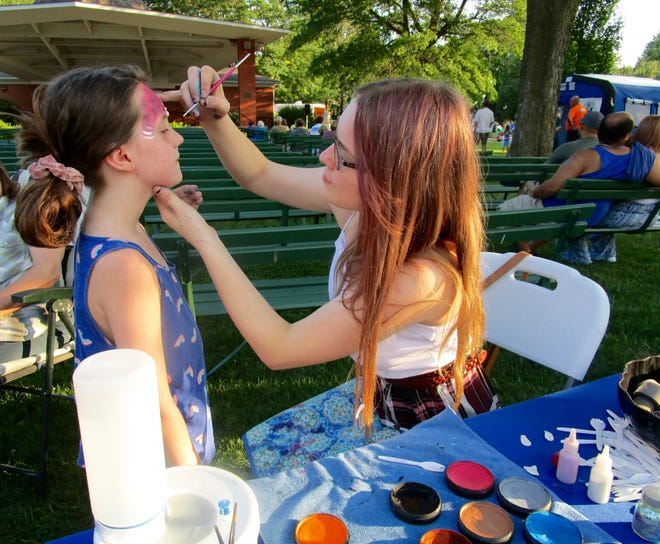 Eight-year-old Remi McKeag was one of the young people who waited in line for a turn to have her face painted by artist Haley Wilson at National Night Out in City Park.