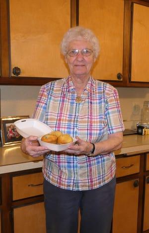 Mildred Schindler Janzen holding home-baked blueberry muffins in her kitchen in Ellsworth.