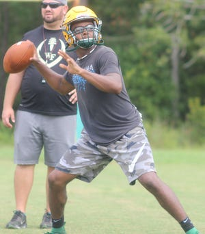 White Oak quarterback Sidney Lee throws a pass during a practice. Lee has been one of the area's best players in recent seasons.