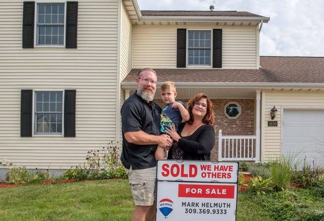 Chris Stevens, his wife, Sarah, and son Walker, 3, stand outside the house they recently sold on Fieldstone in Washington.
